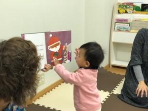 サンタさんの絵の絵本を触っている子の写真