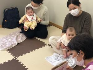 絵本の読み聞かせを聞いている赤ちゃんの画像