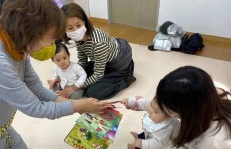 絵本を触ってる赤ちゃんの画像