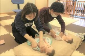 両親教室で赤ちゃんのお着替えの練習をしているプレパパママの画像