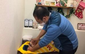 両親教室で赤ちゃんの沐浴後のお世話の練習をしているプレパパの画像
